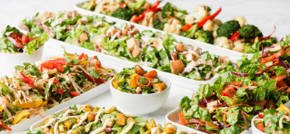 A variety of fresh country salads in a range of white bowls.